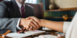 A man wearing a suit and sitting at a wooden desk is building effective workplace relationships with his colleague who is just out of the picture — they are shaking hands.